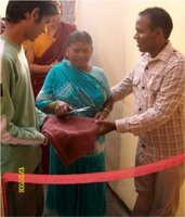 Shashi's mum cutting the ribbon to open the new school, Shashi on the right